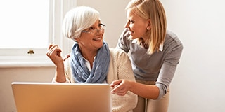A young woman talking to and helping an older woman who is sitting in front of a computer.