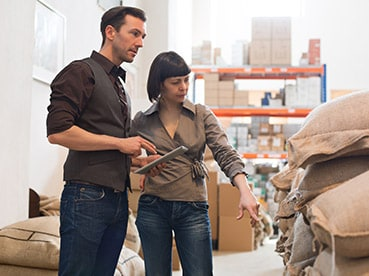 Woman and man in warehouse evaluating products for international trade