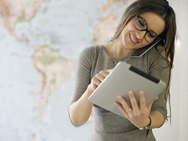 Woman with phone and tablet managing international deliveries